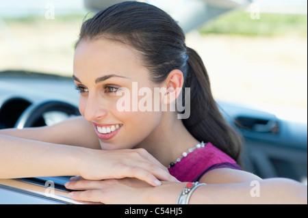 Bella giovane donna appoggiata sul finestrino Foto Stock