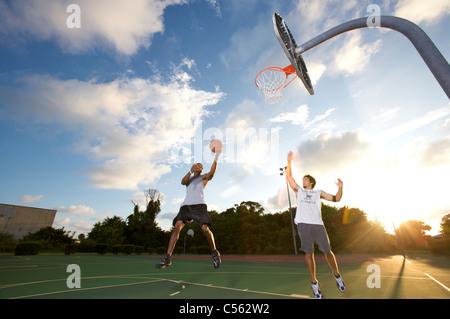 Punteggio maschio durante outdoor basketball scrimmage tra due giovani uomini Foto Stock