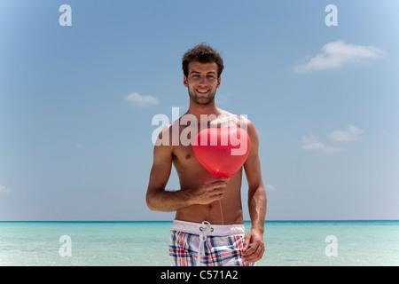 Uomo con cuore palloncino sagomato sulla spiaggia Foto Stock
