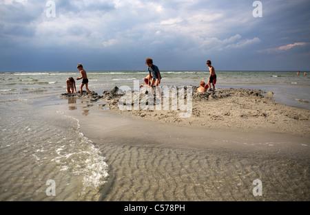 Bambini che giocano nella sabbia sulla spiaggia Foto Stock