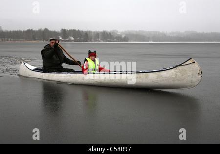 Uomo e bambino seduto in una canoa su un lago ghiacciato Foto Stock