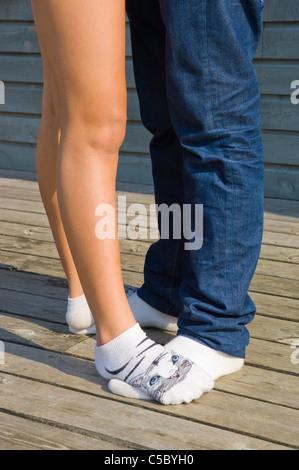 Sezione bassa di un paio di calze con la donna in piedi sull'uomo per le gambe su pannelli di legno di superficie Foto Stock