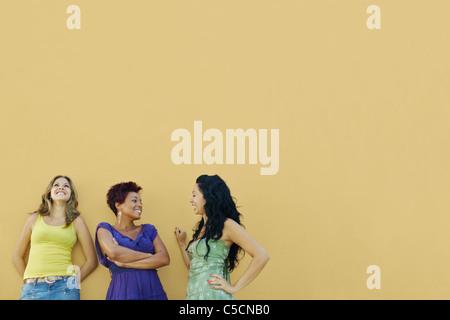 Un gruppo di tre donne amici ispanica appoggiata sulla parete gialla e ridere. Sagoma orizzontale, vita, spazio Foto Stock