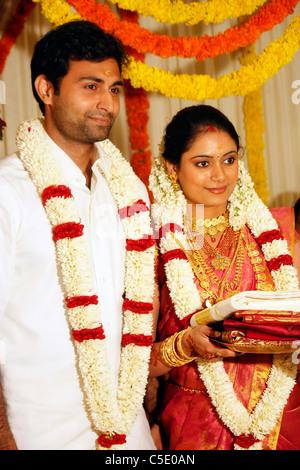 Sposa e lo sposo a piedi dopo la cerimonia del matrimonio in un Indiano nozze indù - tradizionale stile di medicazione Foto Stock