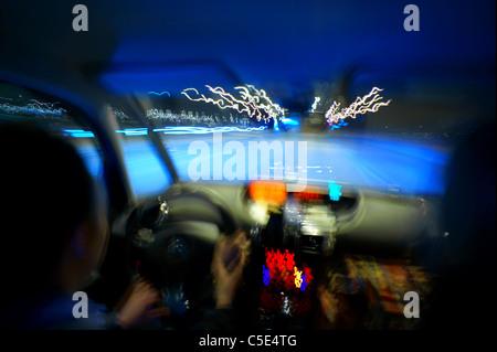 Close-up vista offuscata delle mani sul volante in un auto Foto Stock