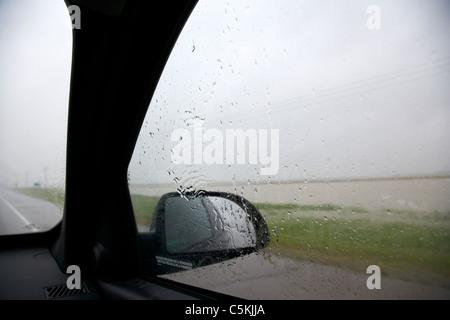 Guardando fuori del car guida attraverso la pioggia torrenziale e delle inondazioni nel sud del Saskatchewan canada Foto Stock