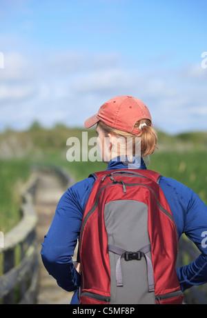 Donna escursionismo su una palude boardwalk. Grassy Narrows Marsh, Manitoba, Canada. Foto Stock