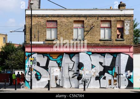 East London street scene non ridondante di business chiuso soggetto ad atti vandalici & intavolato pub edificio Foto Stock