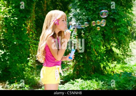 Bambini soffiando bolle di sapone nella foresta esterna con la moda fiore rosa Foto Stock