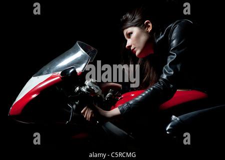 Ritratto di una giovane donna su un motociclo rosso Foto Stock