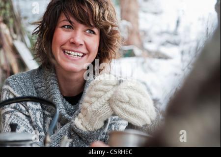 L'Austria, paese di Salisburgo, Flachau, giovane uomo e donna bere il tè e seduta oltre alla stufa in inverno Foto Stock
