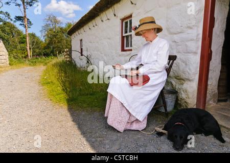 """Donna in irlandese abito vittoriano seduto fuori da un cottage mentre """""""" di carda lana con una spazzola metallica all'Ulster Folk Park Museum Foto Stock"""