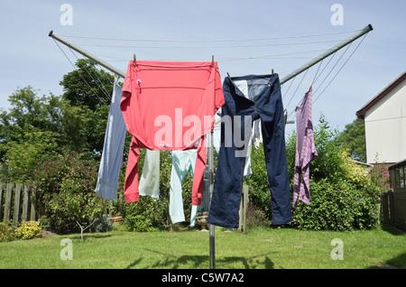 Vestiti bagnati appendere fuori su un rotary linea di lavaggio a secco all'aperto in un giardino in un giorno caldo Foto Stock