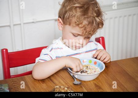 Germania Berlino, ragazzo (3-4) seduti al tavolo e giocare con il cibo, guardando verso il basso, verticale Foto Stock