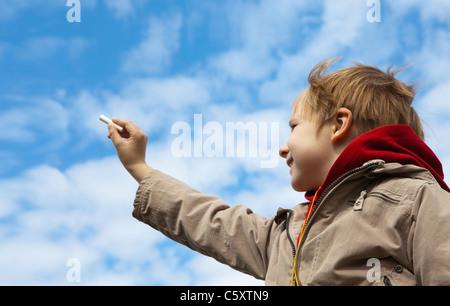 Il ragazzo di disegno di un gesso su cielo nuvoloso Foto Stock