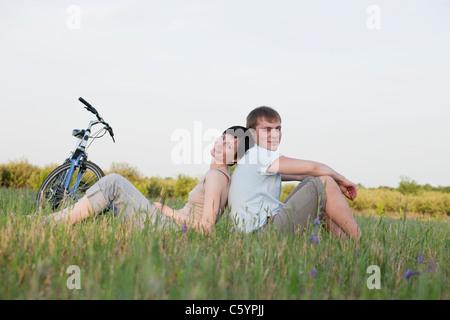 Russia, Voronezh, giovane seduto in Prato Foto Stock