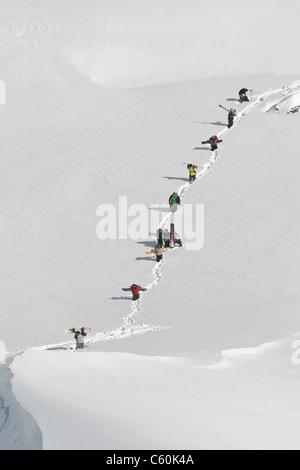 Gli appassionati di snowboard a camminare su pendio di montagna Foto Stock