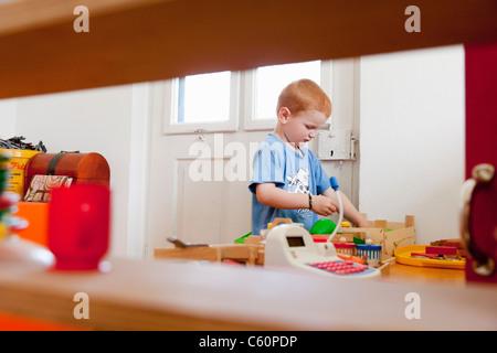 Ragazzo giocando con i giocattoli in salotto Foto Stock