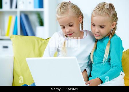Ritratto di twin ragazze che studiano nella parte anteriore del computer portatile Foto Stock