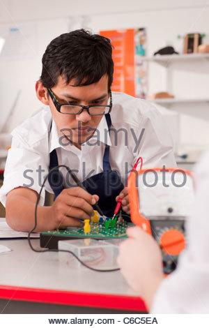 Gli studenti che lavorano sul dispositivo elettronico in classe professionale insieme Foto Stock