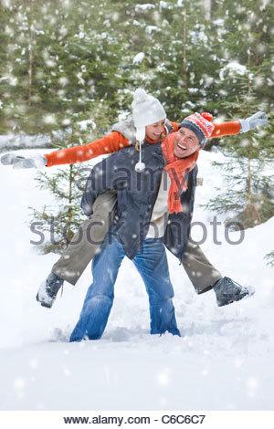 Uomo che porta esuberante donna sul retro in boschi innevati Foto Stock
