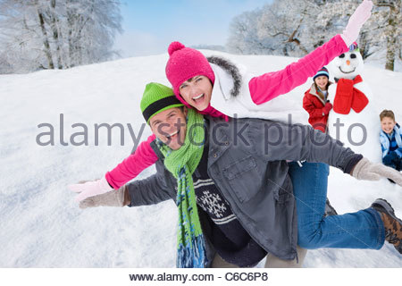 Uomo che porta esuberante donna sulla schiena e i bambini con pupazzo di neve in background Foto Stock
