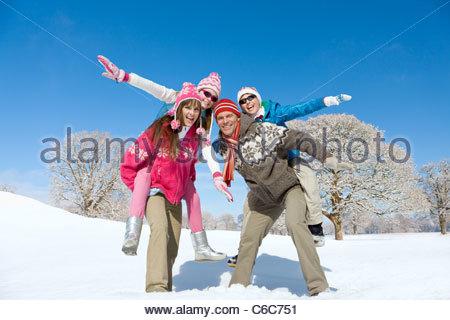 I genitori che trasportano esuberante bambini sul retro in posizione soleggiata, campo nevoso Foto Stock