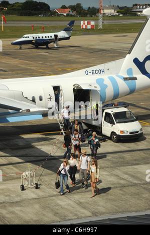 Un Dash-8 G-ECOH off caricando i passeggeri a Guernsey Airport con un blu isole G-ISLB BAe 3202 Jetstream 31 in Foto Stock
