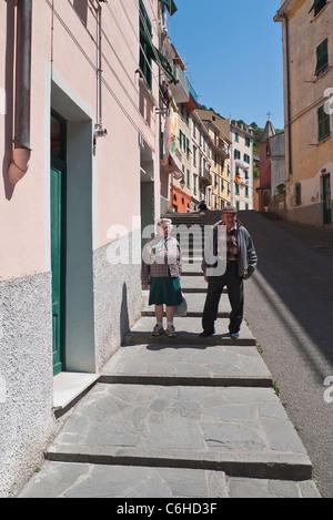 Un anziana coppia italiana parla e gesto come essi camminare sul marciapiede nel loro villaggio di Riomaggiore, Cinque Terre, Italia.