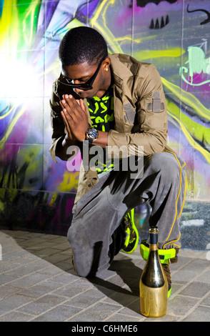 Afro-americano offre preghiere davanti di colorati graffiti wall Foto Stock