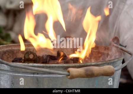 Primo piano delle fiamme provenienti da un piccolo barbecue come il carbone si riscalda Foto Stock