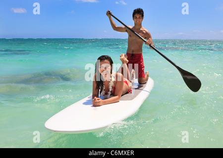 Coppia giovane con la loro scheda di racchetta in Hawaii Foto Stock