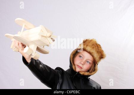 Una giovane ragazza fingendo di essere un pilota durante la riproduzione con un giocattolo di legno piano. Piano Foto Stock