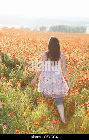 Donna che cammina nel campo dei fiori Foto Stock