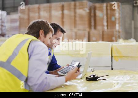 Lavoratori che utilizzano computer portatile in magazzino