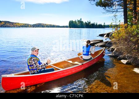 La famiglia in canoa rossa vicino alla spiaggia rocciosa del Lago dei due fiumi, Ontario, Canada Foto Stock