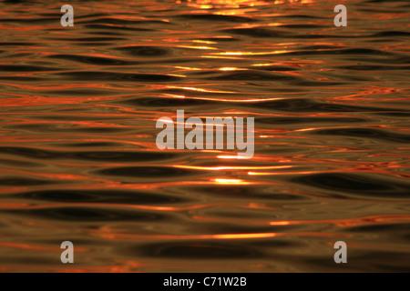 Arancione tramonto riflesso su acqua con texture di ondulazione Foto Stock