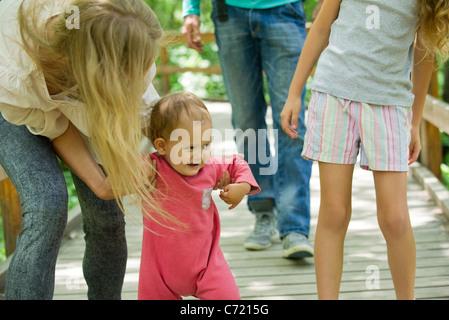 Baby girl ad imparare a camminare all'aperto con la famiglia Foto Stock