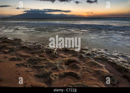 Un bellissimo tramonto su una spiaggia di Maui con le onde che lambiscono sui coralli sulla spiaggia Foto Stock