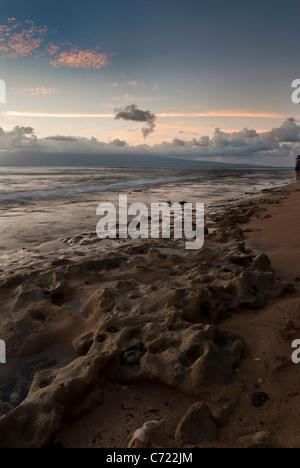 Tramonto su una bella spiaggia di Maui con le nuvole in lontananza e onde che lambiscono sui coralli sulla spiaggia Foto Stock