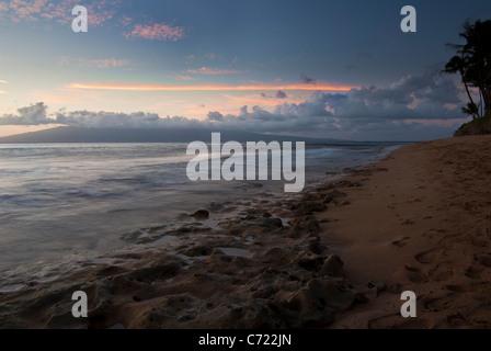 Un bellissimo tramonto in Maui con nuvole in lontananza e onde che lambiscono sui coralli sulla spiaggia Foto Stock