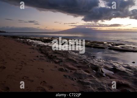 Tramonto su una spiaggia di Maui, HI con il corallo esposti sulla spiaggia Foto Stock