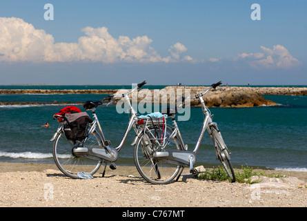 Due biciclette parcheggiate presso le rive del Mediterraneo vicino a Saintes Maries de la Mer, Francia Foto Stock