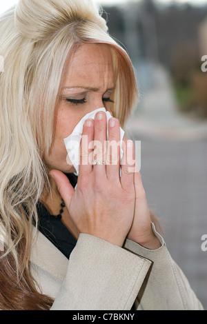 Questa giovane donna di starnuti ripetuti in un tessuto o ha un raffreddore o veramente male le allergie. Foto Stock