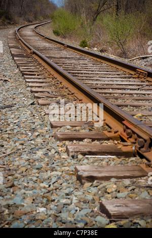 I binari della ferrovia della curvatura fuori nella distanza avanti. Foto Stock