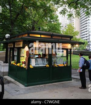 Uomo che guarda il verde Ferrara Cafè Italiano gelato chiosco, mercanti Plaza Gate, West Avenue, al Central Park Foto Stock