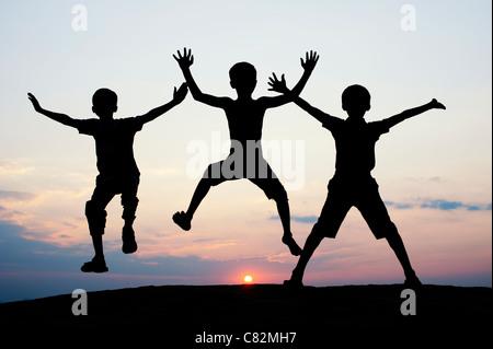 Silhouette di giovani ragazzi indiani jumping contro al tramonto. India Foto Stock
