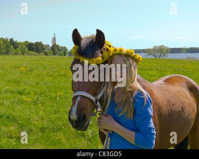 Ragazza giovane con il suo pony in piedi in un campo di fronte ad un lago. ghirlanda di fiori su entrambi le ragazze e il pony alla testa.