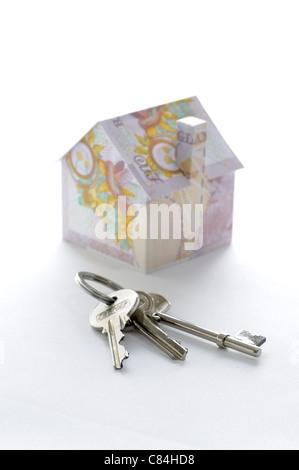 Mazzo di chiavi e modello di casa piegato con British pound banconote Foto Stock