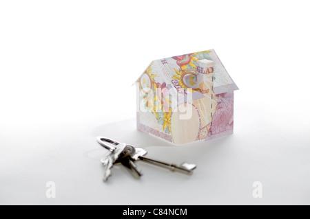 Modello di casa piegato con British pound banconote e le chiavi Foto Stock